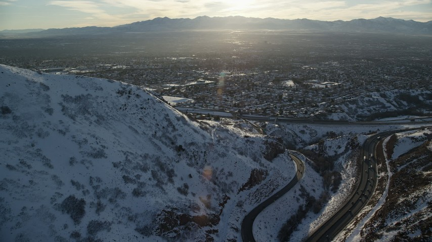 6K stock footage aerial video approach Salt Lake City suburbs from snowy Wasatch Range mountains at sunset, Utah Aerial Stock Footage | AX127_073