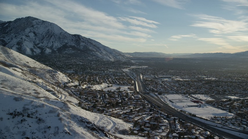6K stock footage aerial video of suburban neighborhoods at the foot of snowy mountains in Salt Lake City at sunset, Utah Aerial Stock Footage | AX127_074