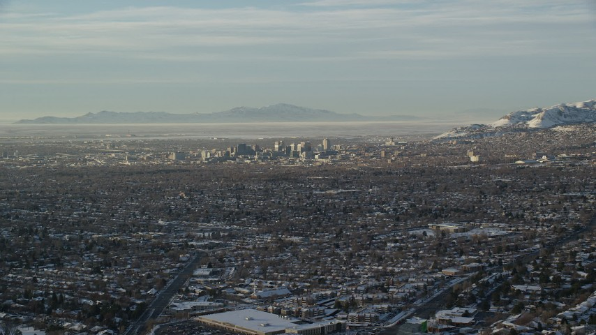 6K stock footage aerial video of a view of Downtown Salt Lake City across suburban neighborhoods in winter at sunset, Utah Aerial Stock Footage | AX127_075