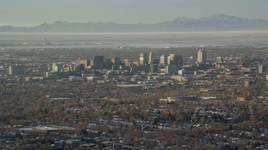 6K stock footage aerial video orbit Downtown Salt Lake City buildings in winter at sunset with the airport in the background, Utah Aerial Stock Footage | AX127_079