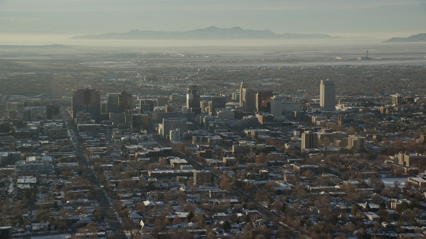 6K stock footage aerial video of Downtown Salt Lake City with winter snow seen from east of the city at sunset, Utah Aerial Stock Footage | AX127_084