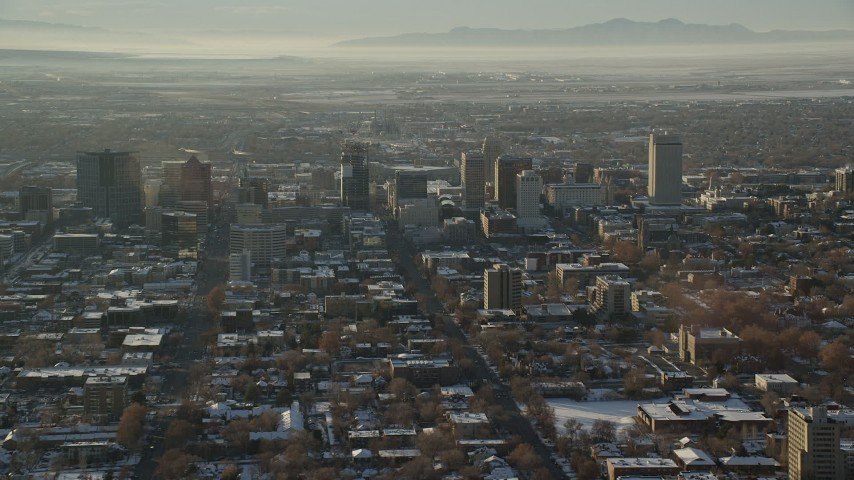6K stock footage aerial video orbit buildings in Downtown Salt Lake City with winter snow at sunset in Utah Aerial Stock Footage | AX127_085