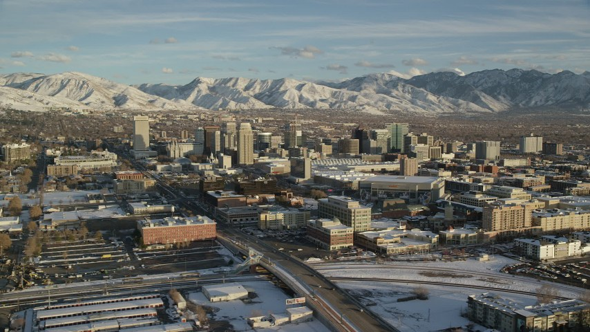 6K stock footage aerial video orbiting Downtown Salt Lake City buildings with winter snow at sunset, Utah Aerial Stock Footage | AX127_095