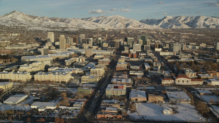 6K stock footage aerial video of buildings in Downtown Salt Lake City with winter snow at sunset in Utah Aerial Stock Footage | AX127_097
