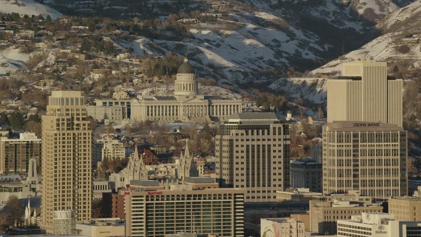 Orbit Utah State Capitol seen between Downtown Buildings at Sunset in Wintertime Aerial Stock Footage | AX127_101