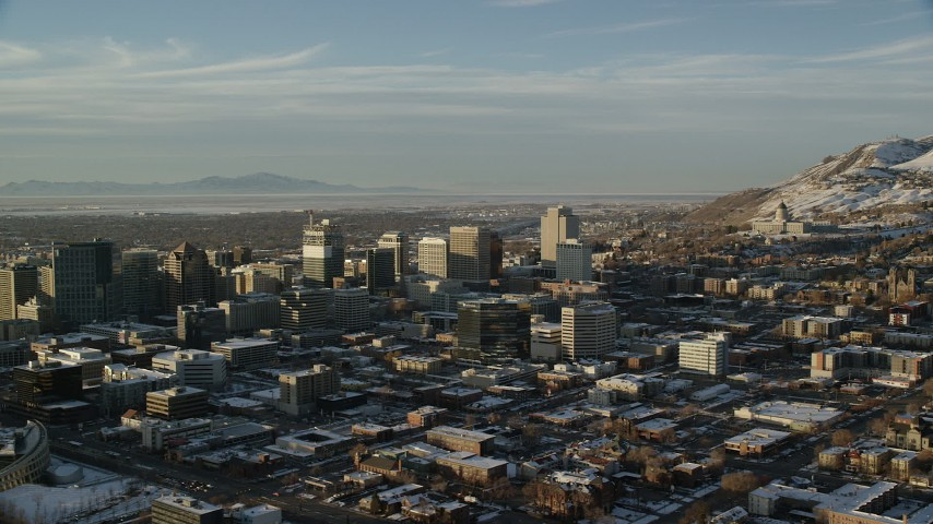 6K stock footage video of passing by Downtown Salt Lake City near Utah State Capitol with winter snow at sunset Aerial Stock Footage | AX127_106
