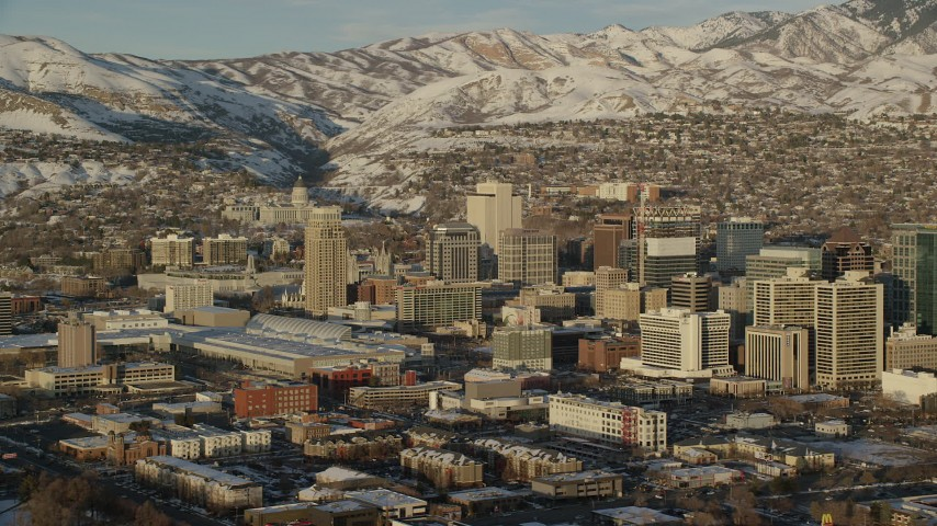 6K stock footage aerial video view northeast across Downtown Salt Lake City to snow mountains while orbiting at sunset, Utah Aerial Stock Footage | AX127_112
