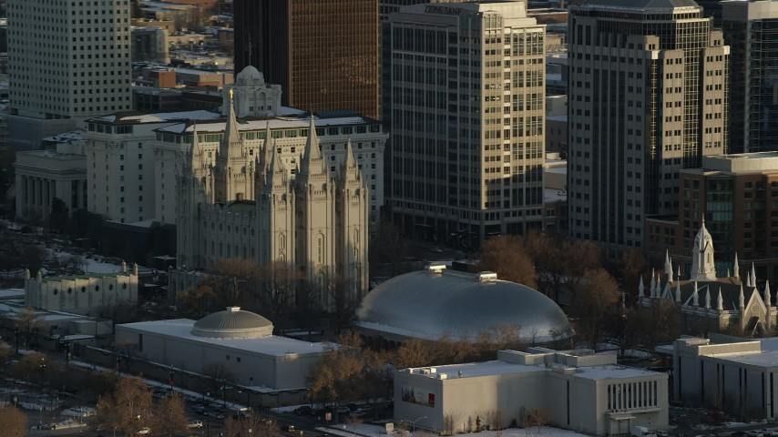 6K stock footage aerial video orbit Salt Lake Temple and Tabernacle at sunset with winter snow, Salt Lake City, Utah Aerial Stock Footage | AX127_118