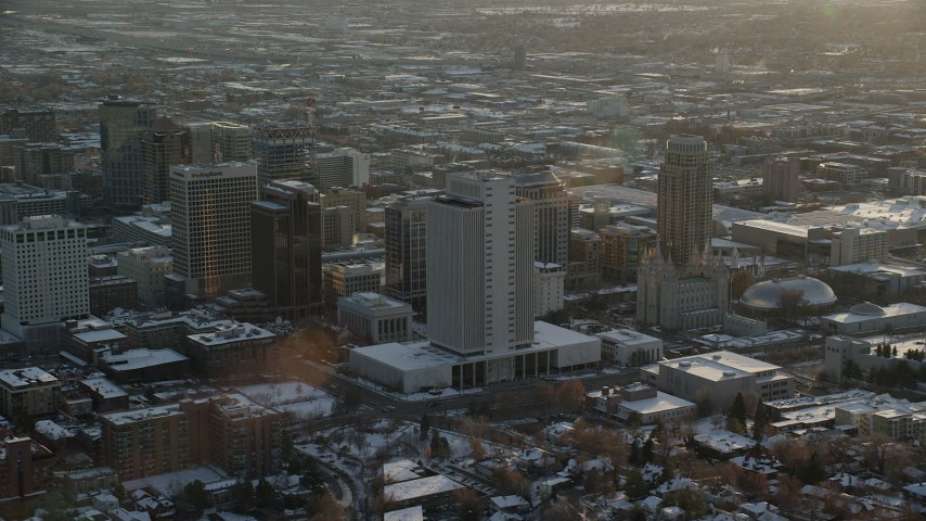 6K stock footage aerial video orbit tall buildings by Salt Lake Temple in downtown at sunset with winter snow, Utah Aerial Stock Footage | AX127_124