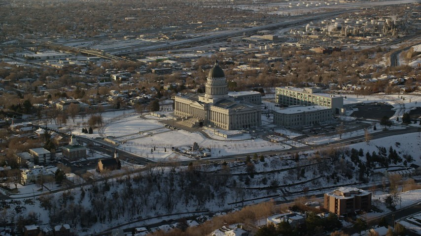 6K stock footage aerial video reverse view of the Utah State Capitol at sunset with winter snow, Salt Lake City Aerial Stock Footage | AX127_125