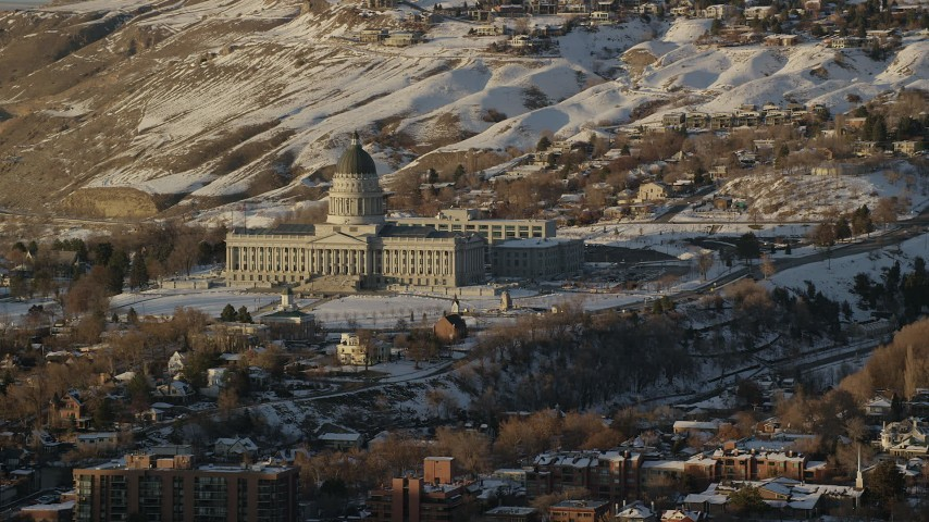 6K stock footage aerial video reverse view of the Utah State Capitol at sunset with winter snow on the ground, Salt Lake City Aerial Stock Footage | AX127_127