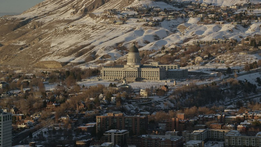 6K stock footage aerial video of reverse view of Utah State Capitol from downtown with winter snow at sunset, Salt Lake City Aerial Stock Footage | AX127_128