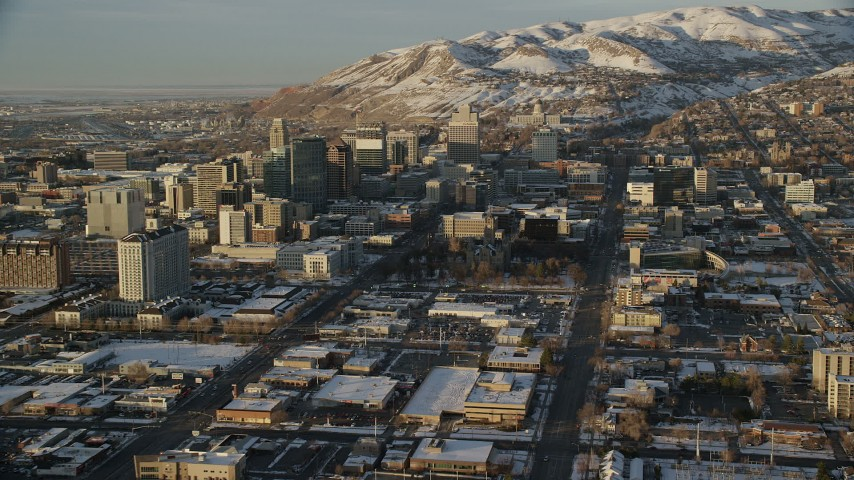 6K stock footage aerial video reverse view of streets through Downtown Salt Lake City to Utah State Capitol at sunset with winter snow Aerial Stock Footage | AX127_130