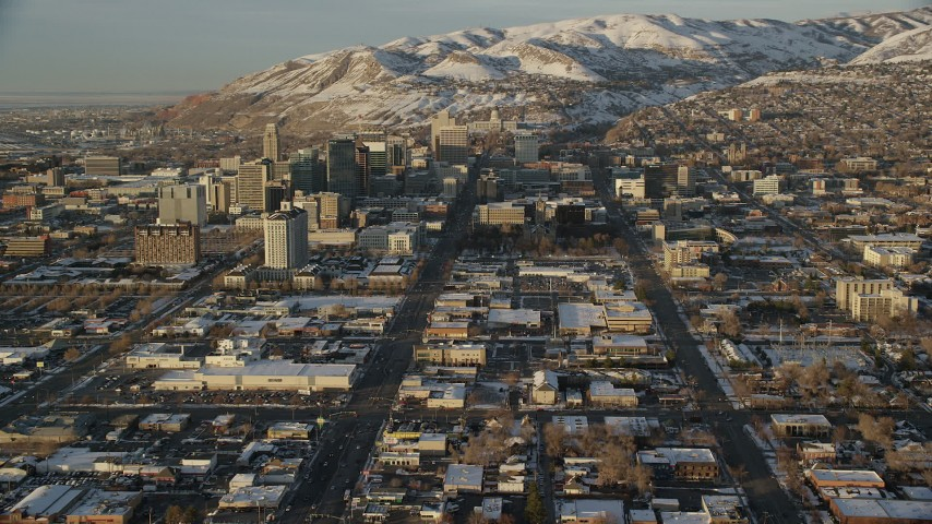 6K stock footage video of reverse view of wide streets through Downtown Salt Lake City at sunset in winter, Utah Aerial Stock Footage | AX127_131