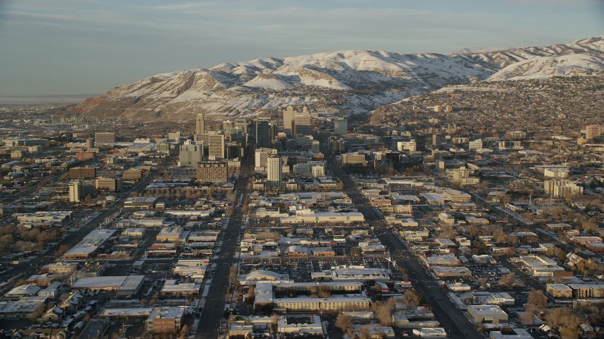 6K stock footage aerial video of wide city streets through Downtown Salt Lake City at sunset with winter snow, Utah Aerial Stock Footage | AX127_132