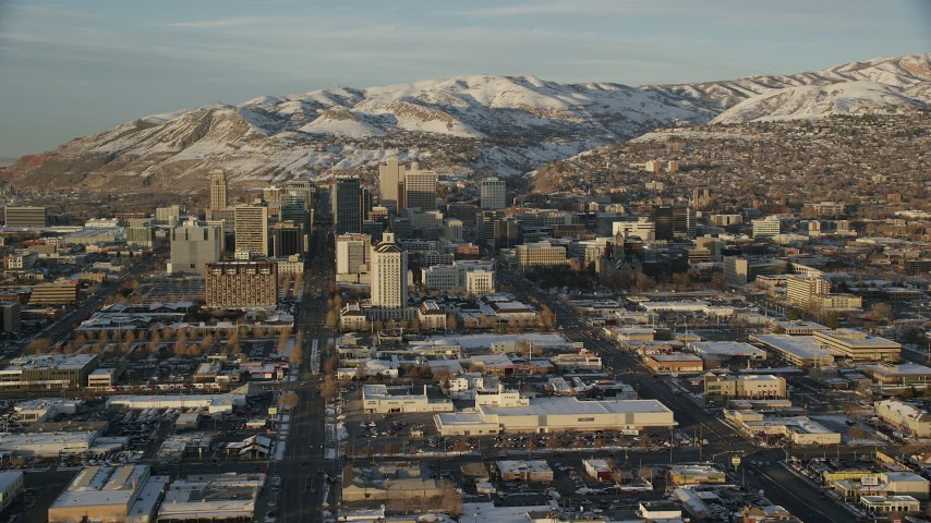 6K stock footage aerial video approach Downtown Salt Lake City between Main and State Streets at sunset with winter snow, Utah Aerial Stock Footage AX127_134 | Axiom Images