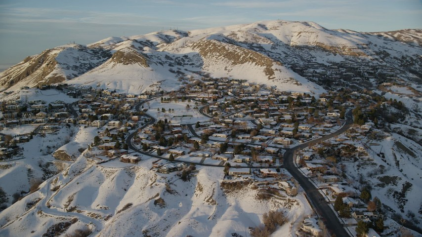 6K stock footage aerial video approach and flyby hillside neighborhood by snowy slopes at sunset, Salt Lake City, Utah Aerial Stock Footage | AX127_143