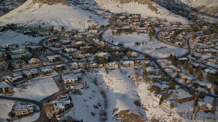 6K stock footage aerial video orbit hilltop homes with snowy yards at sunset, Salt Lake City, Utah Aerial Stock Footage | AX127_144