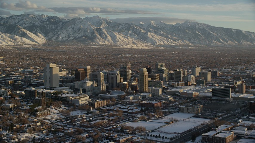 Orbit of Downtown Buildings and Distant Snow Mountains at Sunset in Winter Aerial Stock Footage | AX127_145