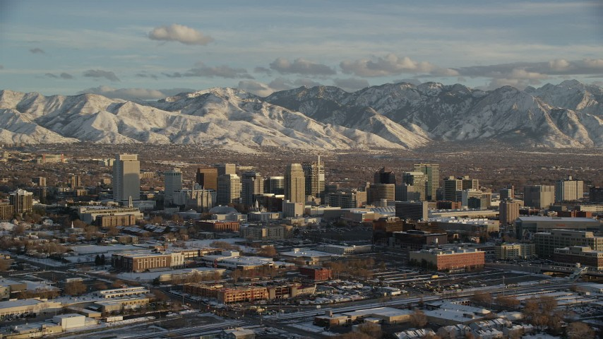 6K stock footage aerial video of orbiting Downtown Salt Lake City with distant snow mountains at sunset in wintertime, Utah Aerial Stock Footage AX127_147