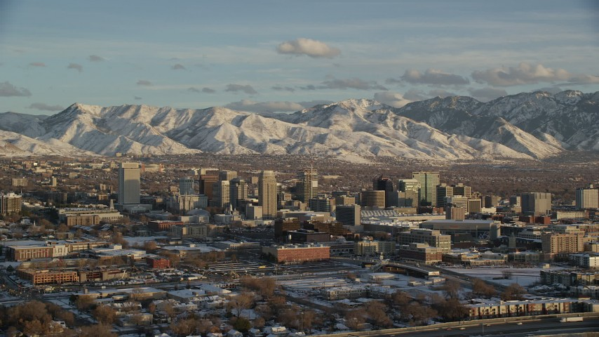 6K stock footage aerial video of orbiting the city and distant mountains with snow at sunset in winter, Salt Lake City, Utah Aerial Stock Footage | AX127_148