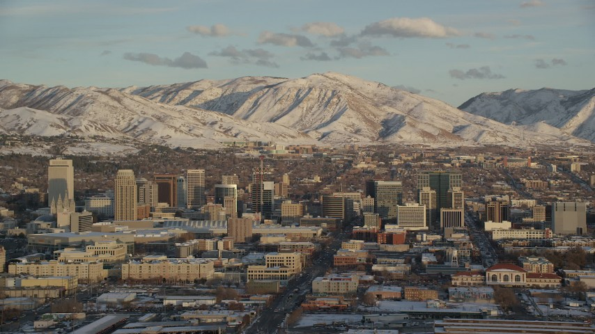 Downtown Area of Salt Lake City and Snowy Mountains at Sunset Aerial Stock Footage | AX127_151
