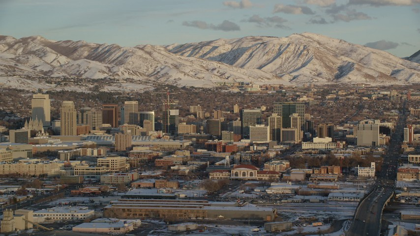 Tall Buildings in Downtown Salt Lake City and Distant Mountains with Snow at Sunset Aerial Stock Footage | AX127_152