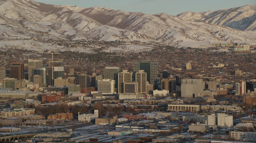 6K stock footage aerial video of tall buildings in Downtown Salt Lake City and frozen mountains in the background at sunset, Utah Aerial Stock Footage | AX127_153