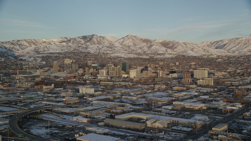 6K stock footage aerial video of Downtown Salt Lake City's tall buildings and distant snow mountains at sunset in winter, Utah Aerial Stock Footage | AX127_154