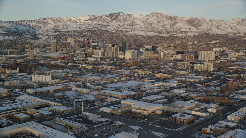 6K stock footage aerial video of Downtown Salt Lake City seen from warehouse buildings at winter sunset, Utah Aerial Stock Footage | AX127_155