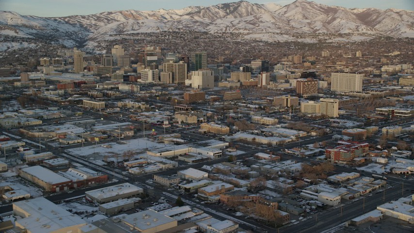 6K stock footage aerial video of Downtown Salt Lake City seen while flying by warehouse buildings at sunset in winter, Utah Aerial Stock Footage | AX127_156