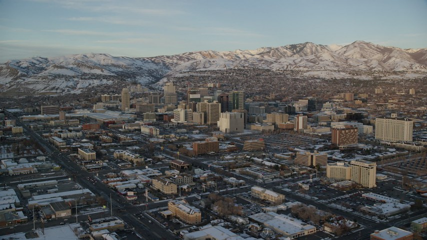 Approach and Flyby Downtown Salt Lake City with Winter Snow at Sunset Aerial Stock Footage | AX127_157