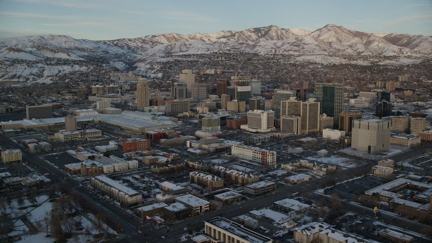 6K stock footage aerial video of Downtown Salt Lake City buildings and convention center with winter snow at sunset, Utah Aerial Stock Footage | AX127_159