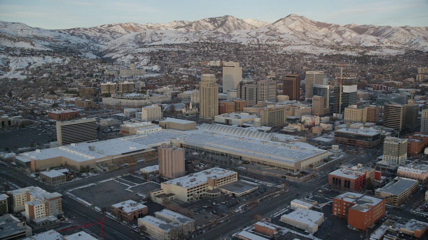 6K stock footage aerial video of Salt Palace and Downtown Salt Lake City buildings with winter snow at sunset, Utah Aerial Stock Footage | AX127_160