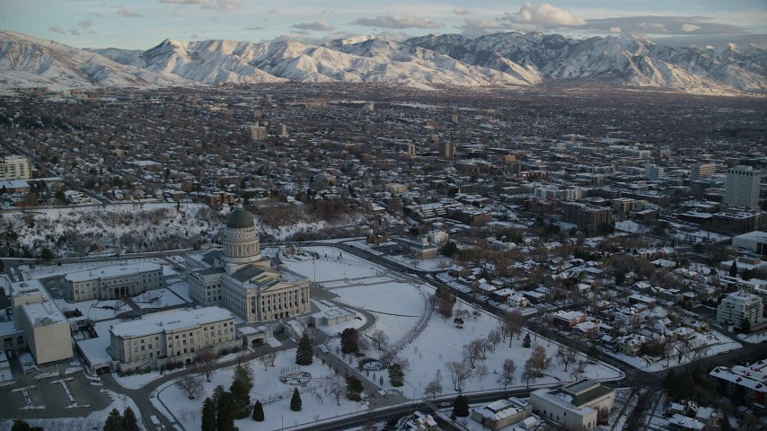 6K stock footage aerial video orbit Utah State Capitol building to reveal Downtown Salt Lake City at sunset with winter snow Aerial Stock Footage | AX127_163