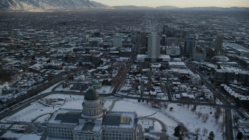 6K stock footage aerial video orbit back of Utah State Capitol with view of Downtown Salt Lake City with snow at sunset Aerial Stock Footage | AX127_164