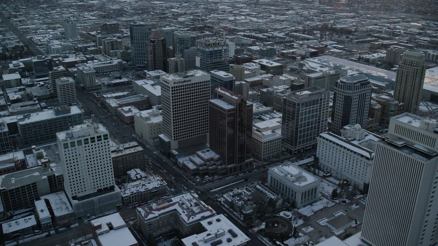 6K stock footage aerial video orbit office buildings in Downtown Salt Lake City at sunset with winter snow, Utah Aerial Stock Footage | AX127_166