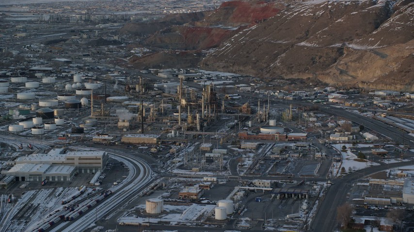 6K stock footage aerial video orbit Tesoro Refinery in Salt Lake City at sunset with winter snow, Utah Aerial Stock Footage | AX127_167