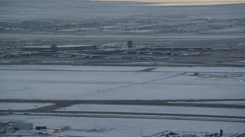 6K stock footage aerial video orbit airport runway as airliner lifts off in background at sunset with winter snow, Salt Lake City, Utah Aerial Stock Footage | AX127_171