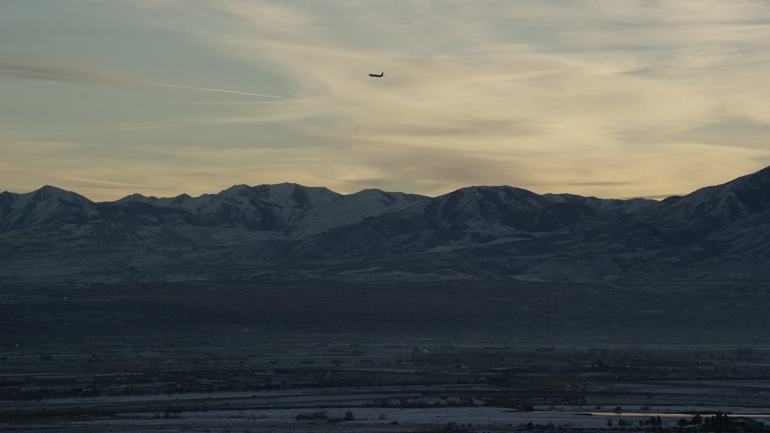 Track Commercial Jet over Snowy Mountains by Salt Lake City at Sunset in Winter Aerial Stock Footage | AX127_174