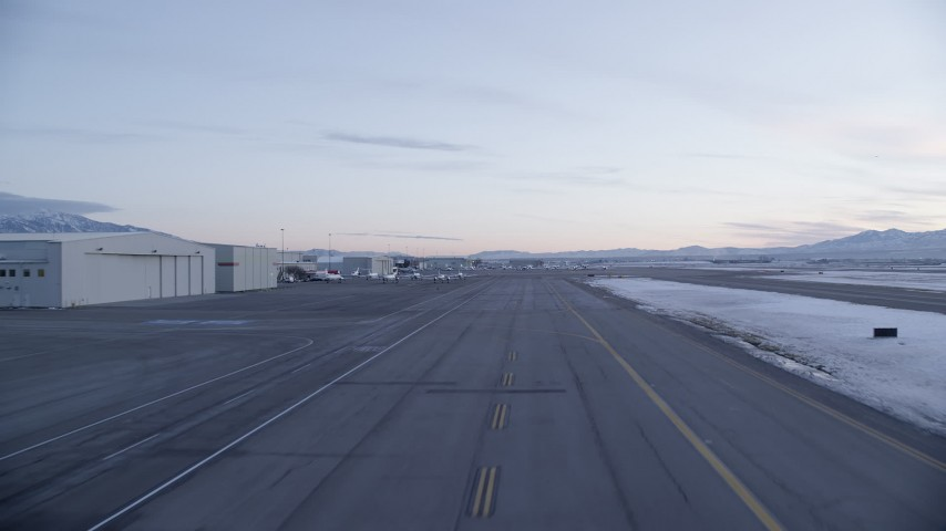 Ascending near Hangars and Parked Planes at SLC Airport in Winter at Sunset Aerial Stock Footage | AX128_004