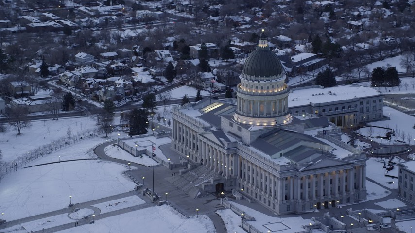 6K stock footage aerial video of orbiting the Utah State Capitol with flag flying and winter snow at twilight, Salt Lake City Aerial Stock Footage   AX128_009