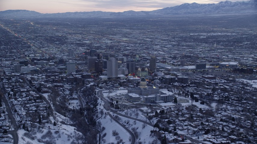 Orbit North Side of the State Capitol Building and Downtown SLC with Winter Snow at Sunset Aerial Stock Footage | AX128_015