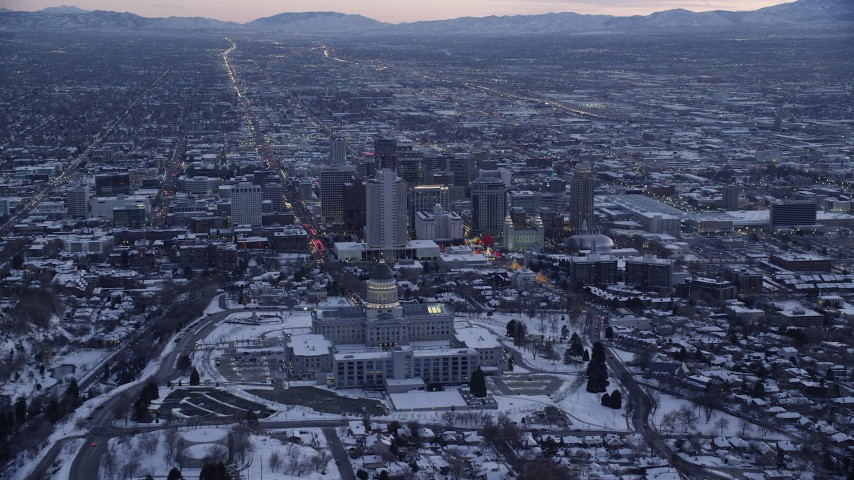 6K stock footage aerial video approach north side of Utah State Capitol and Downtown SLC with winter snow at twilight Aerial Stock Footage | AX128_016