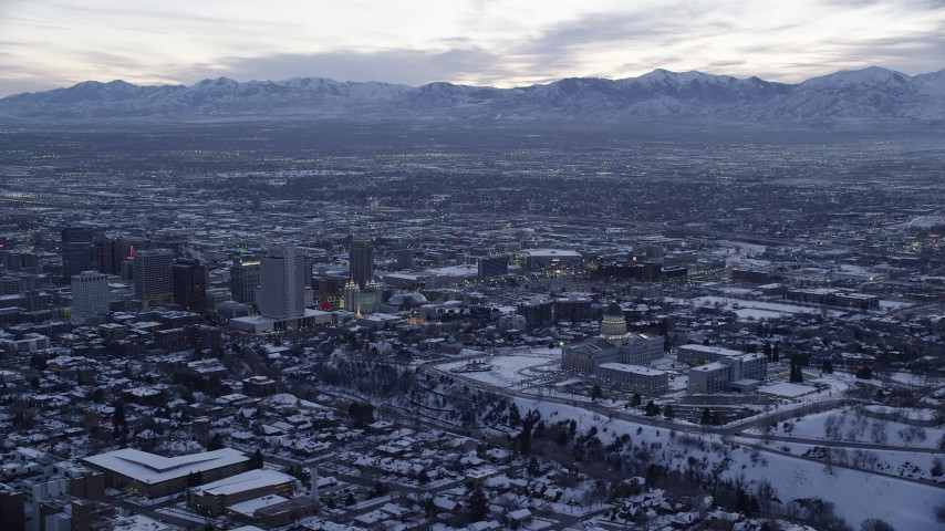 6K stock footage aerial video of a wide orbit of state capitol and Downtown Salt Lake City with winter snow at twilight, Utah Aerial Stock Footage | AX128_020