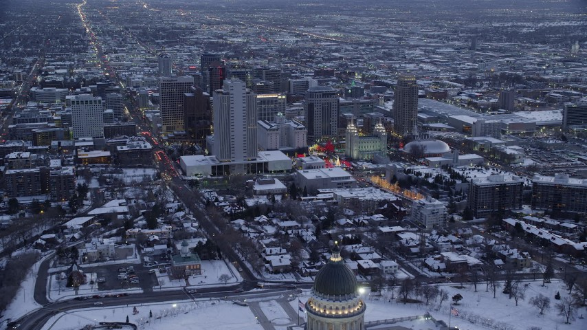 Fly Over State Capitol toward Church Buildings and Temple with Snow at twilight Aerial Stock Footage AX128_023