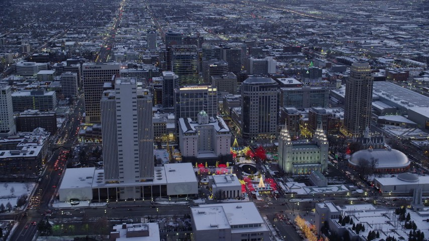 6K stock footage aerial video fly over Salt Lake Temple in Downtown SLC and approach Main Street in winter at twilight, Utah Aerial Stock Footage AX128_024