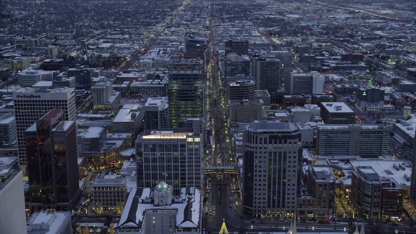 6K stock footage aerial video of following Main Street over office buildings in Downtown Salt Lake City, Utah in winter at twilight Aerial Stock Footage | AX128_025