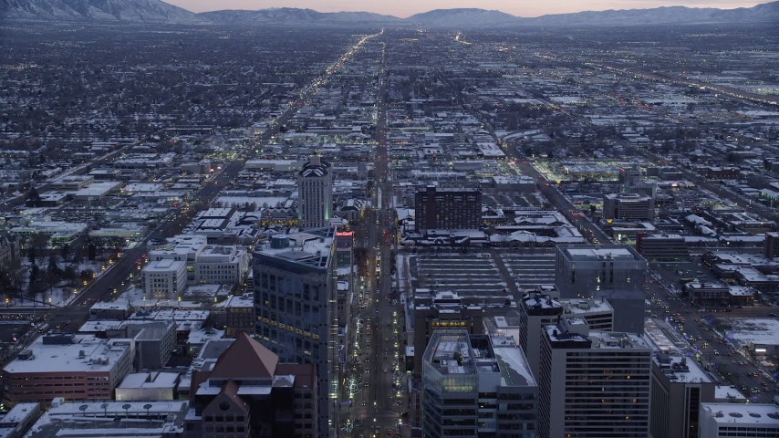 6K stock footage aerial video fly south over Main Street through Downtown Salt Lake City, Utah with winter snow at twilight Aerial Stock Footage | AX128_026