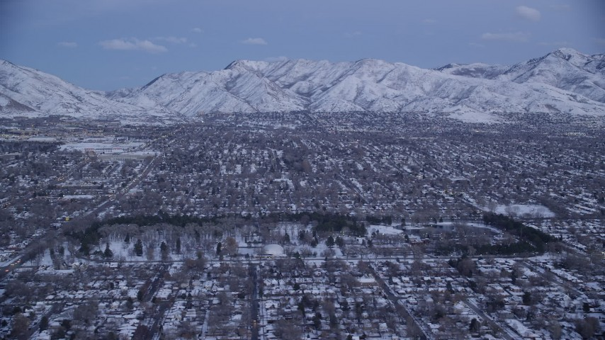 6K stock footage aerial video of suburban Neighborhoods and Liberty Park with winter snow at twilight, Salt Lake City, Utah Aerial Stock Footage | AX128_029